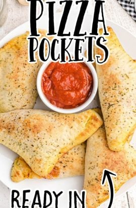 overhead shot of pizza pockets piled on a white plate with dipping pizza sauce in the middle
