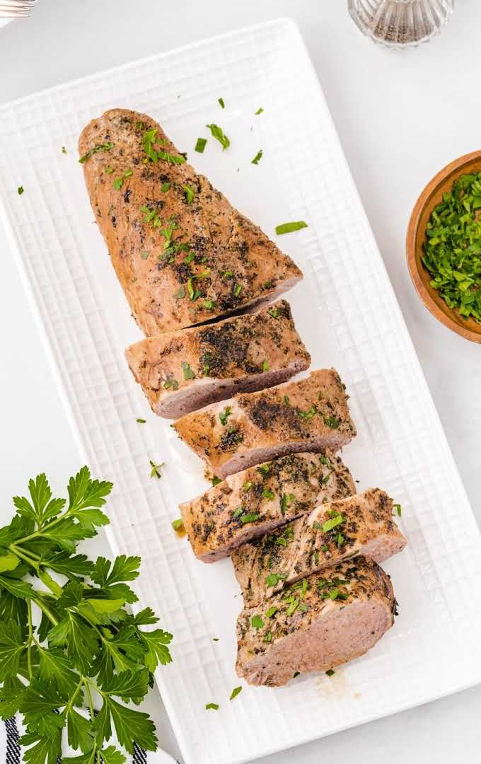 close up overhead shot of pork tenderloin garnished with seasonings and sliced on a white tray