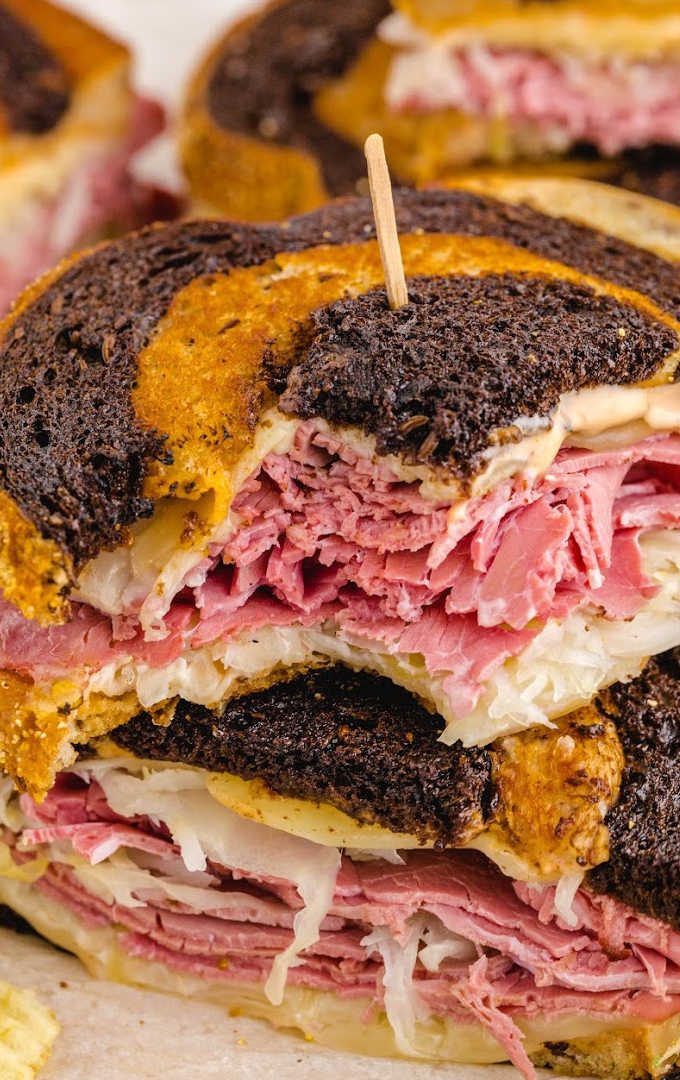 close up shot of reuben sandwich stacked on top of each other