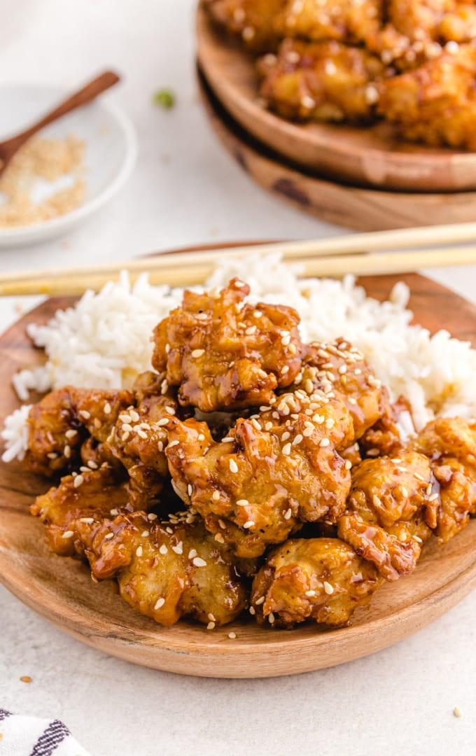 sesame chicken garnished with sesame seeds and served with white rice on a wooden board
