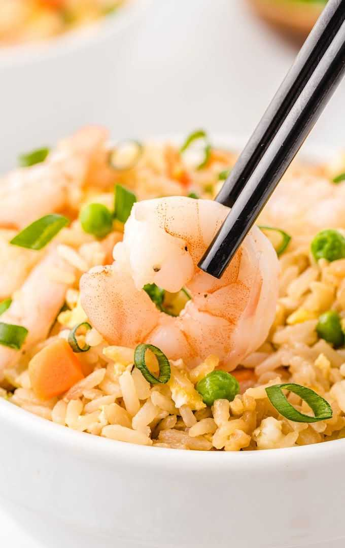 close up shot of shrimp fried rice garnished with green onions in a wooden bowl with shrimp being picked up with chop sticks