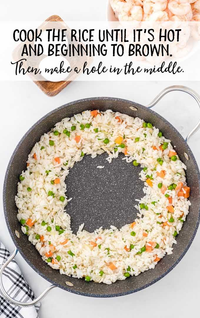 shrimp fried rice process shot of cooked rice in a skillet with a hole in the middle