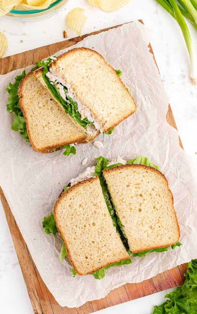 overhead shot of tuna sandwich sliced on a sheet that is placed on a wooden board