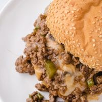 overhead shot of Philly cheesesteak sloppy joes on a white plate