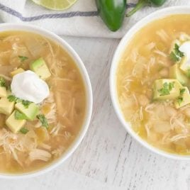 close up overhead shot of 2 bowls of White Bean Chili topped with avocado slices and sour cream
