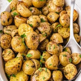 close up overhead shot of garnished oven roasted potatoes in a white dish