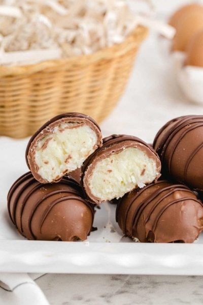 side shot of coconut cream chocolate easter eggs stacked on dish showing their inside coconut layers