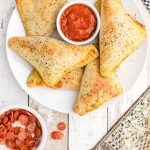 overhead shot of pizza pockets piled on a white plate with dipping sauce in the middle
