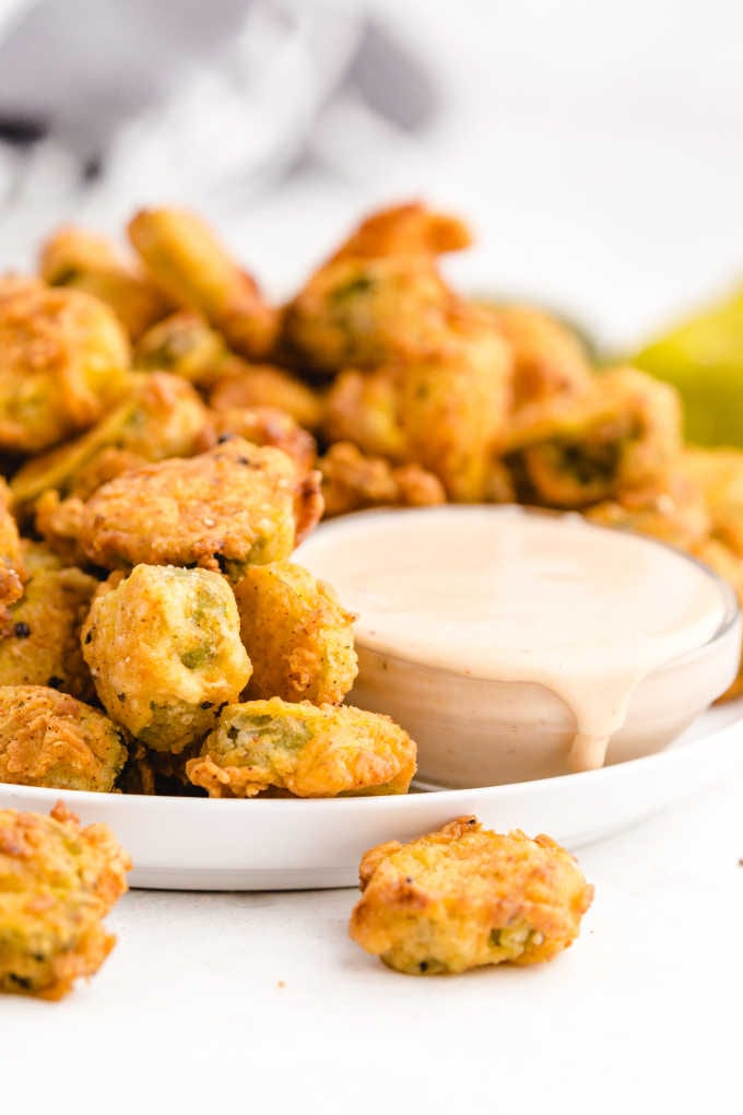 fried pickles stacked on top of each other with dipping sauce on a plate