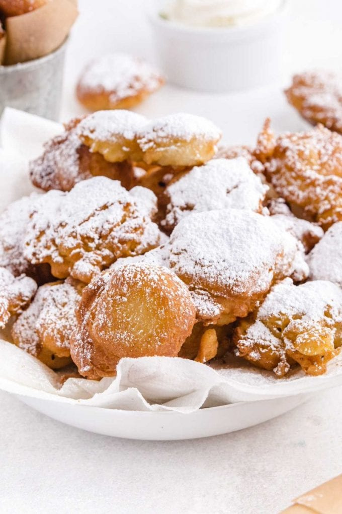 close up shot of funnel cake bites sprinkled with powdered sugar in a white bowl