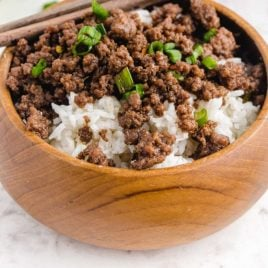 close up shot of korean beef served over rice and garnished with onions in a bowl