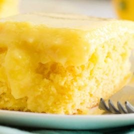 close up side shot of lemon poke cake on a white plate with a fork