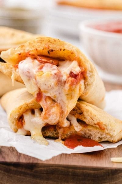 close up shot of pizza pockets pulled apart showing its gooey insides on a board
