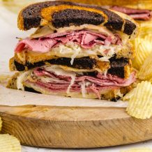 close up side shot of reuben sandwich served with chips on a wooden board