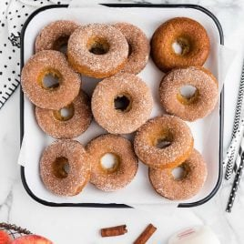 close up overhead shot of Apple Donuts with cinnamon sugar frosting piled on a dish