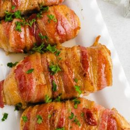 close up overhead shot of Bacon-Wrapped Chicken topped with parsley on a serving tray