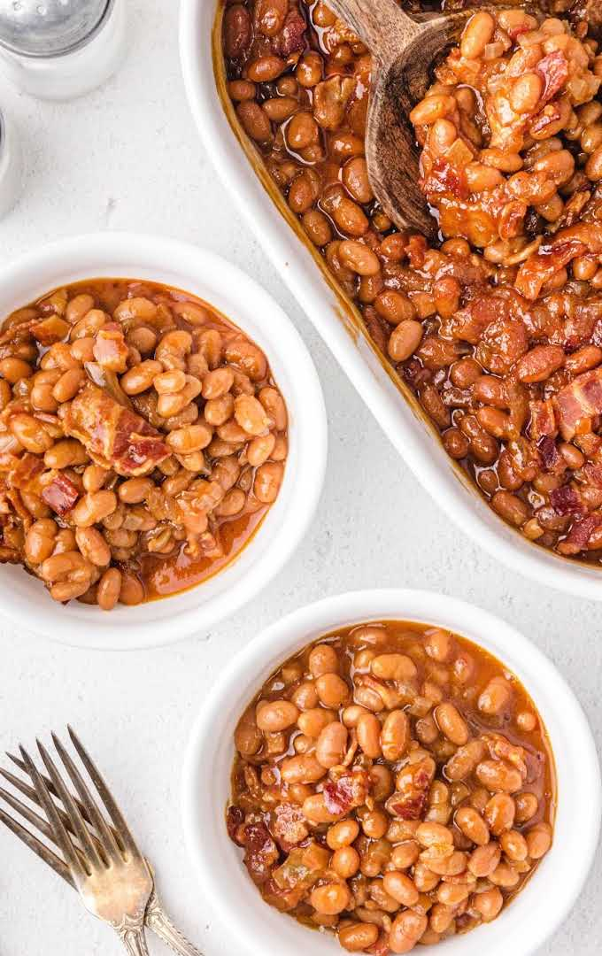 overhead shot of baked beans in white bowls and in a white baking dish with a wooden spoon