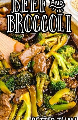 close up overhead shot of beef and broccoli in a pan with a wooden spoon