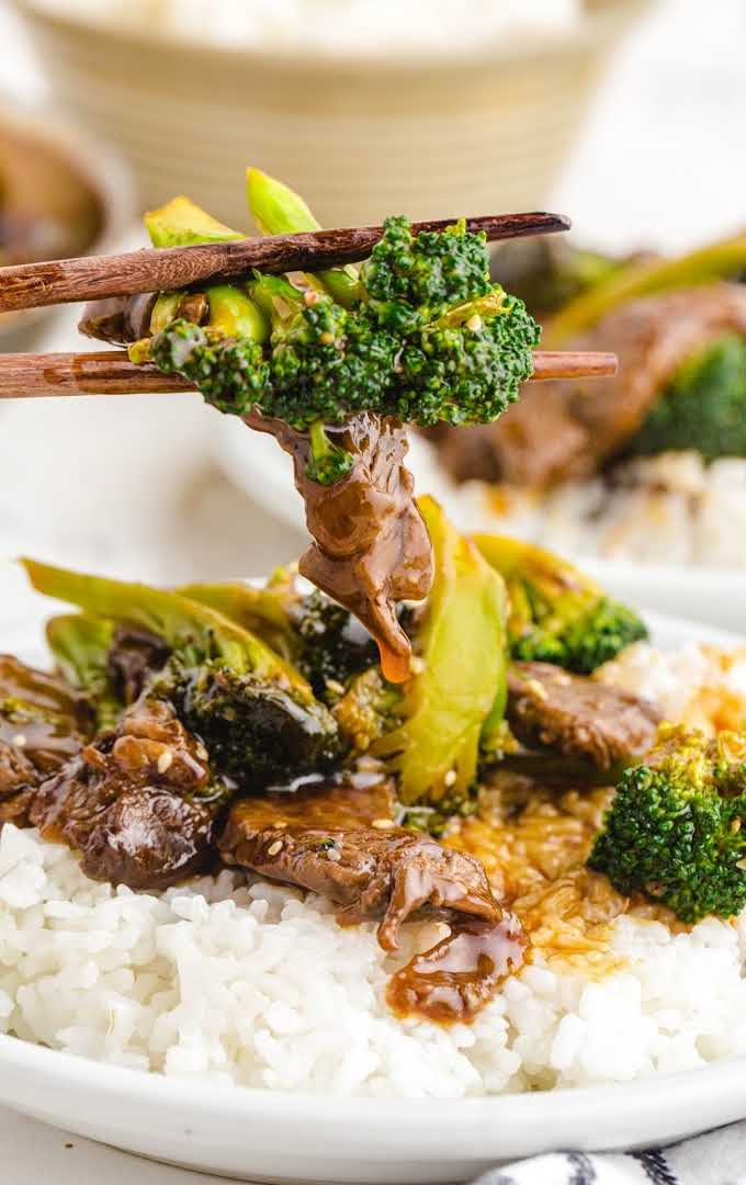 beef and broccoli on a plate of rice being picked up with chopsticks