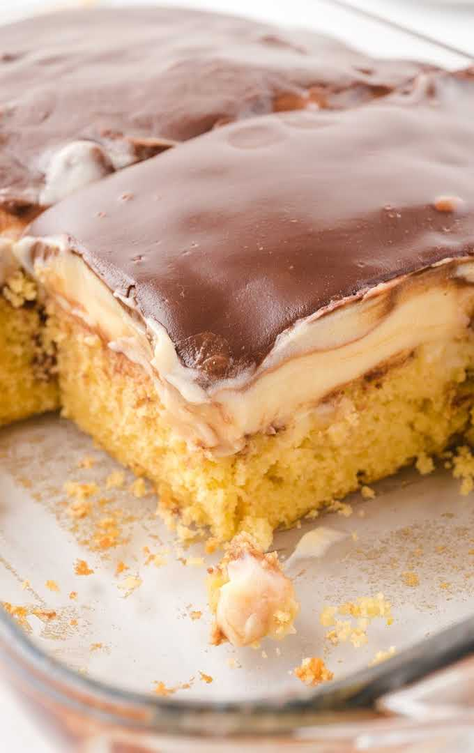 close up shot of boston cream poke cake in a clear baking dish