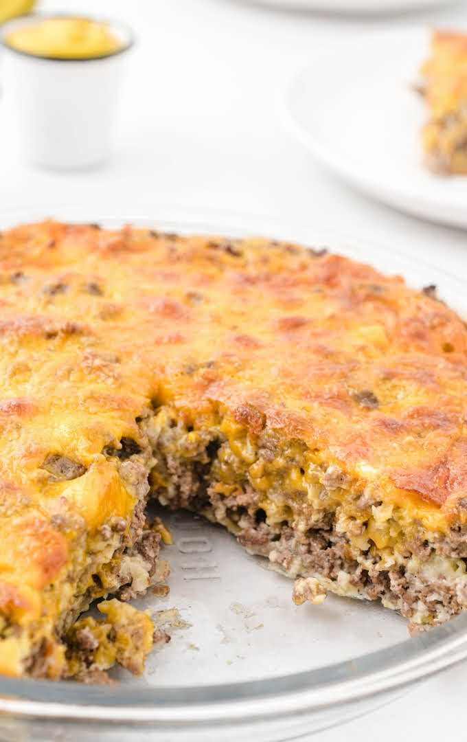 close up shot of cheeseburger pie in a pan with a slice missing showing its inside layers