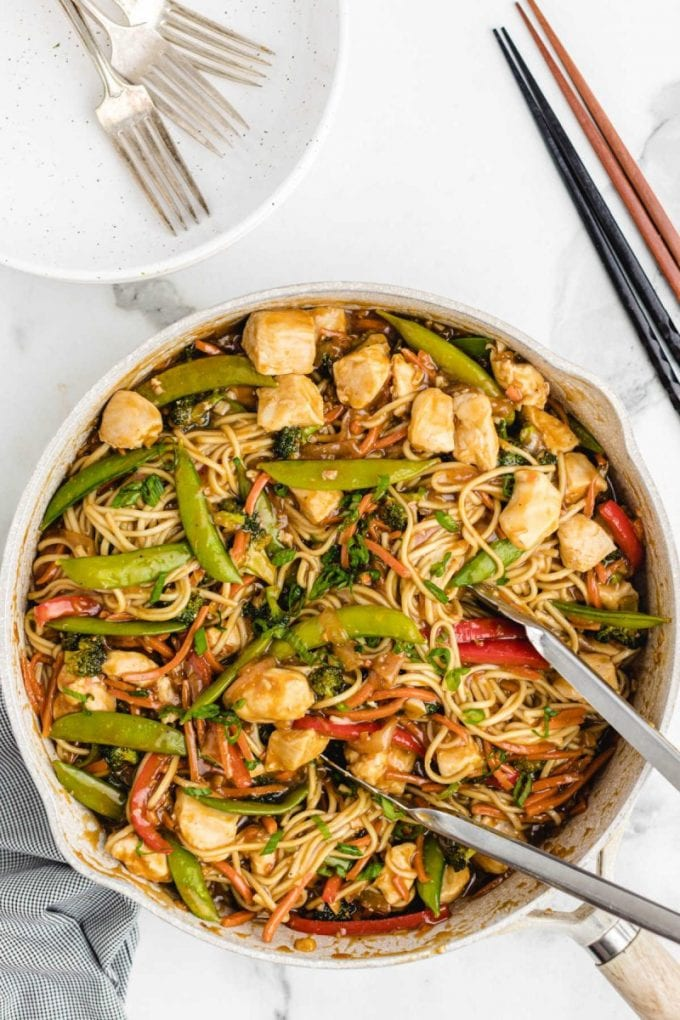 overhead shot of chicken lo mein in a pan with tonsils