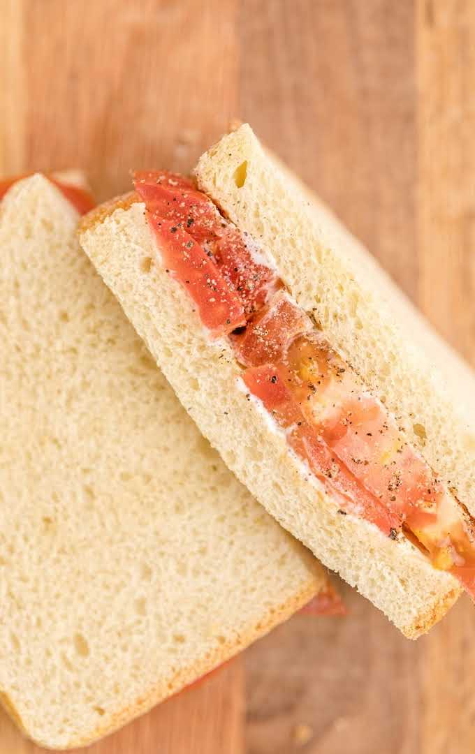 overhead shot of tomato sandwich on a wooden board