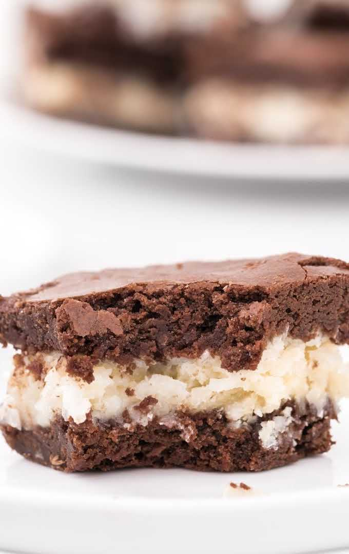 close up shot of coconut brownies with a bite taken out of it