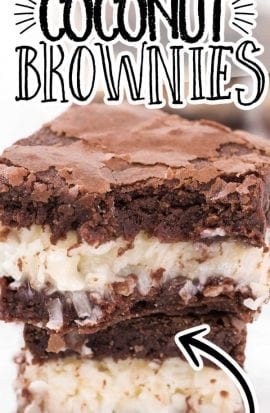 close up shot of coconut brownies stacked on top of each other with a bite taken out of it