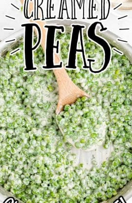 overhead shot of creamed peas in a pan with a large wooden spoon