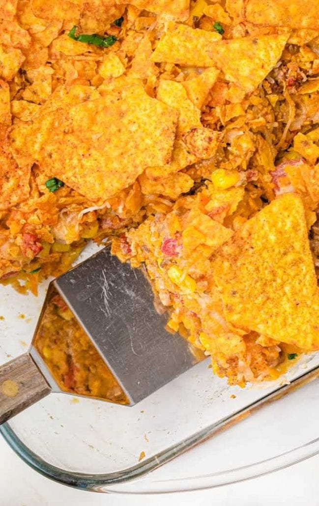 close up shot of doritos casserole in a pan being scooped up with a spatula