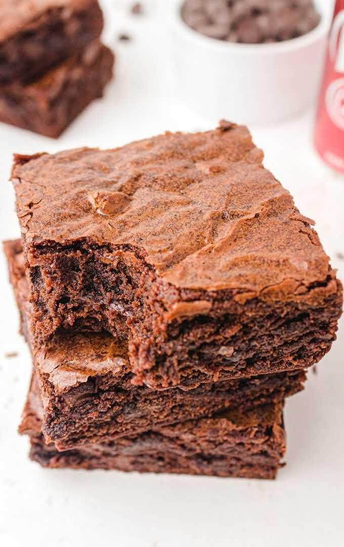 close up shot of Dr Pepper Brownies stacked on top of each other with a bite taken out of the top brownie