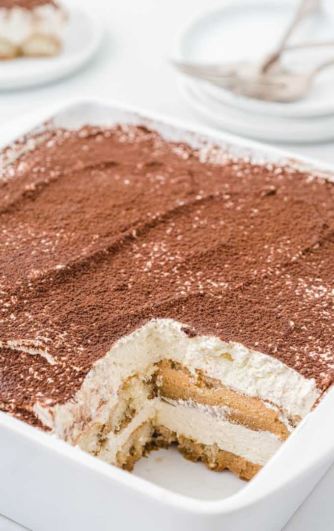 close up shot of easy tiramisu recipe in a baking dish with a slice missing