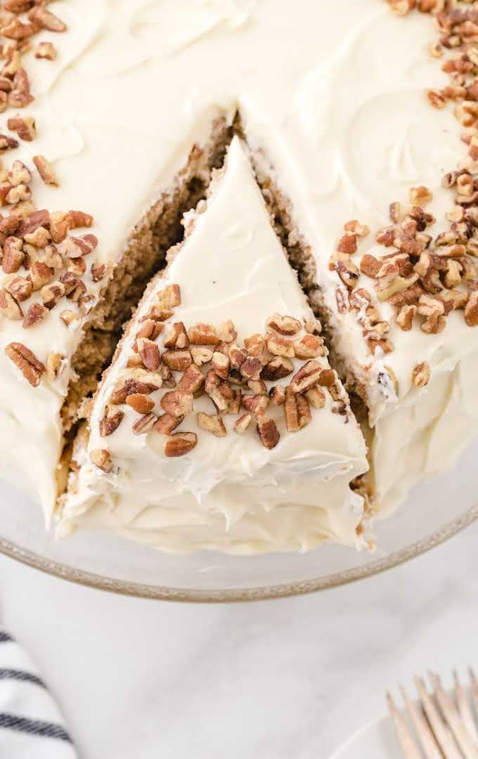 side shot of hummingbird cake with pecans on top with a slice cut out on a cake dish
