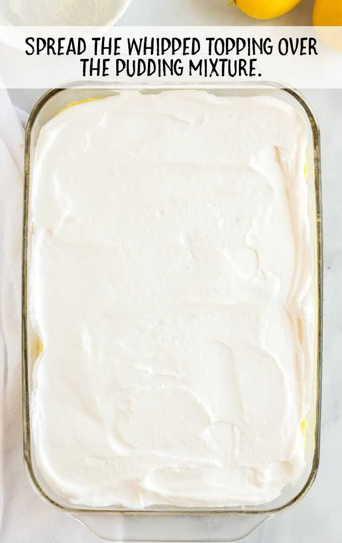 lemon lush process shot of whipped topping being spread over pudding in a pan