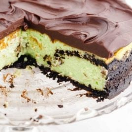 close up shot of mint chocolate cheesecake with a slice taken out of it on a cake dish