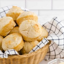 No Yeast Dinner Rolls in a bread basket with a side of butter and a roll on a plate