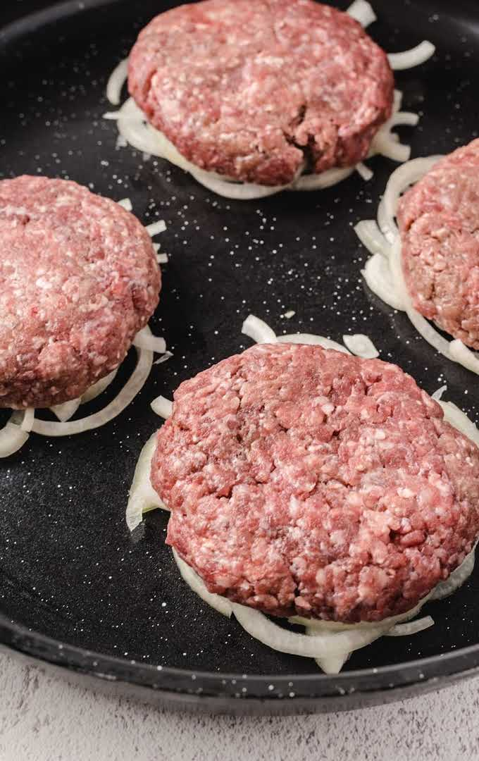 close up shot of Oklahoma Fried Onion Burgers raw and laid on top of onions on a skillet