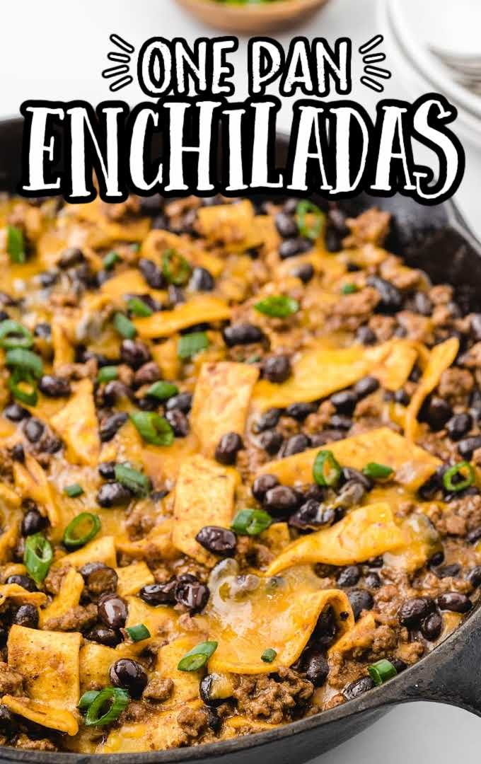 overhead shot of skillet enchiladas garnished with green onions in a skillet with a wooden spatula