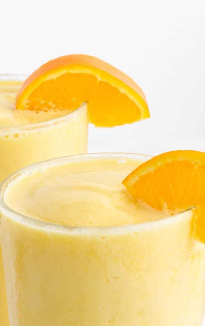 close up shot of orange julius in glasses garnished with a slice of orange