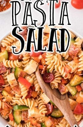 close up overhead shot of pasta salad in a bowl with a wooden spoon