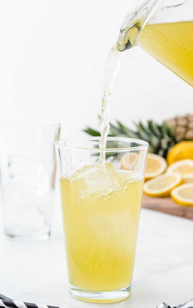 a pitcher of pineapple lemonade being poured into a glass of ice