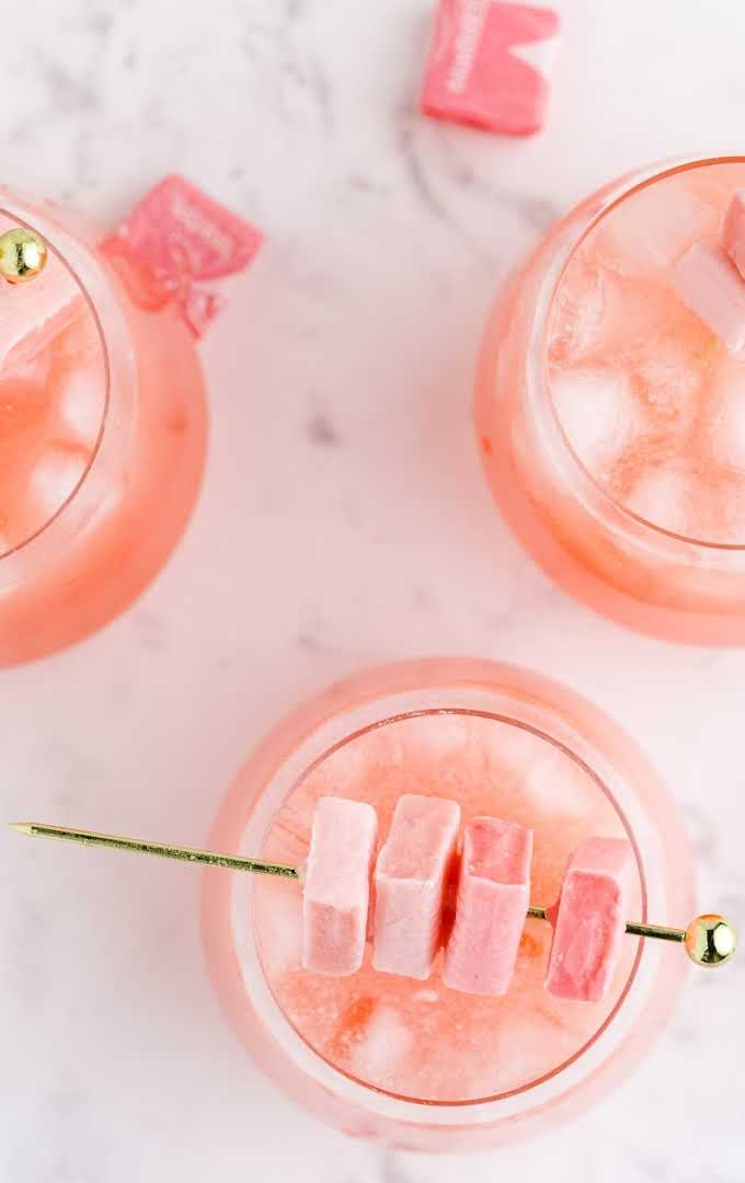 overhead shot of pink starburst cocktail with starburst candy in glasses