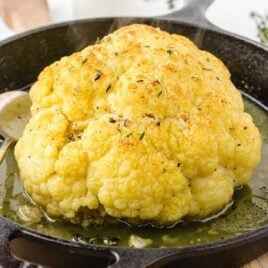 close up shot of the head of a Roasted Cauliflower topped with thyme in a skillet with a spoon