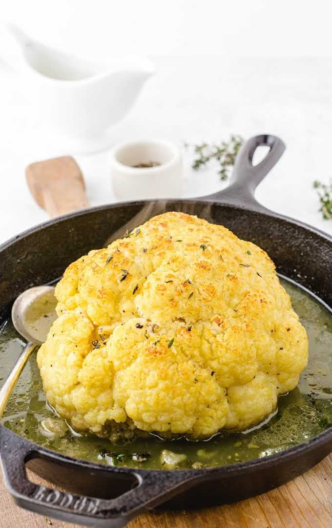 roasted cauliflower in a pot of broth with a spoon