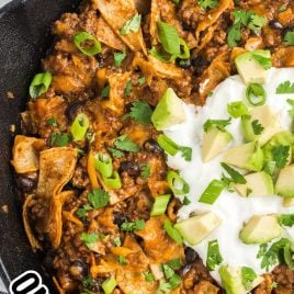 close up overhead shot of a skillet of Skillet Enchiladas topped with green onions, cilantro, sour cream, and avocado