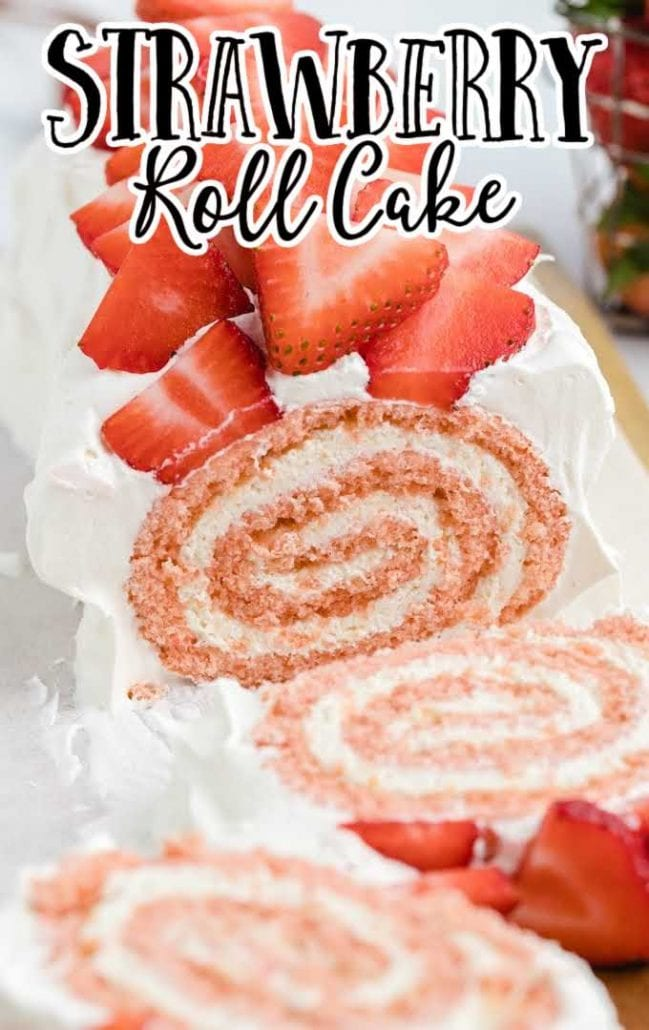close up shot of strawberry roll cake garnished with diced strawberries and cut into slices on a wooden board