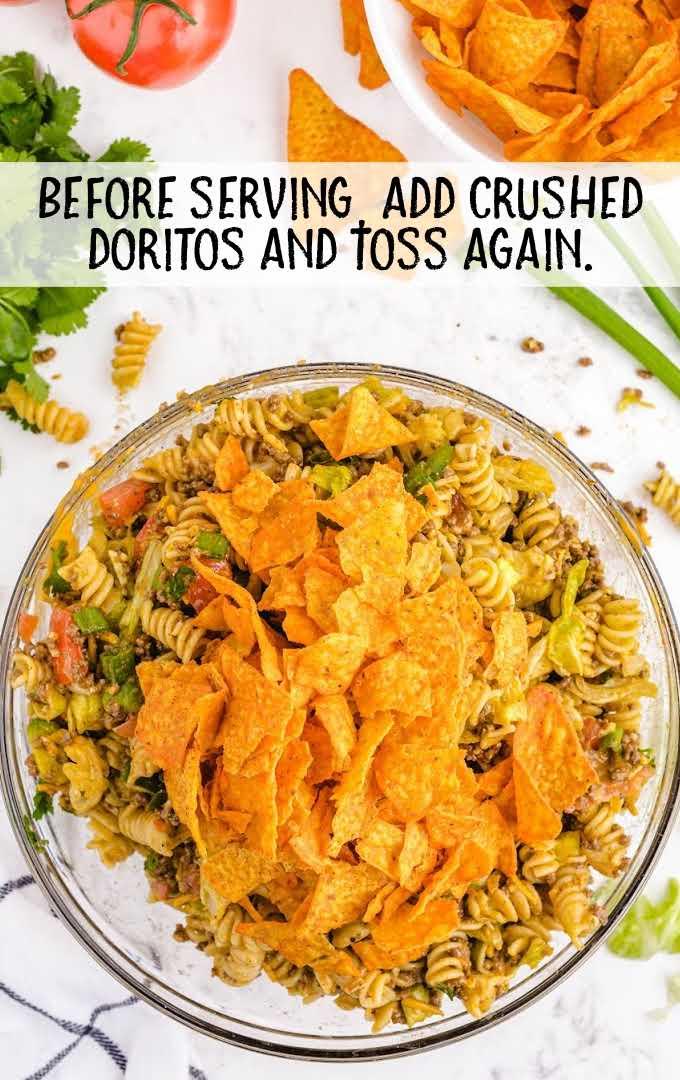 taco pasta salad process shot of crushed doritos being added to salad