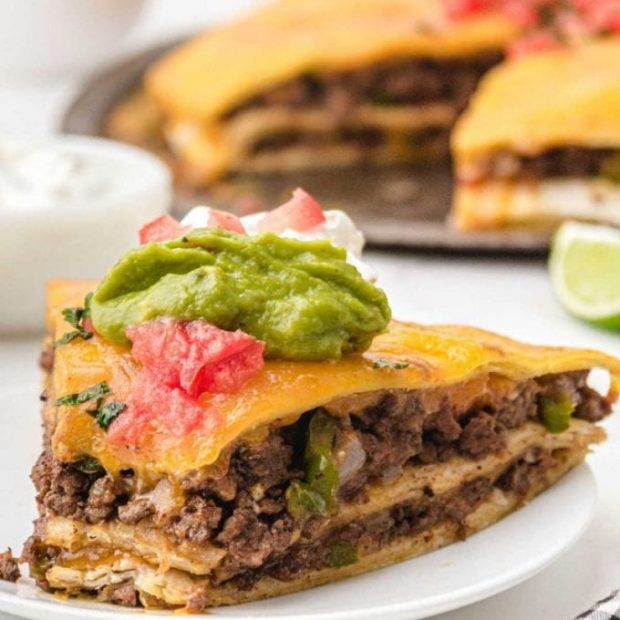 side shot of Taco Pie topped with guacamole, cream cheese, and salsa on a plate