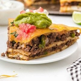 close up side shot of Taco Pie on a plate topped with guacamole, cream cheese, and salsa